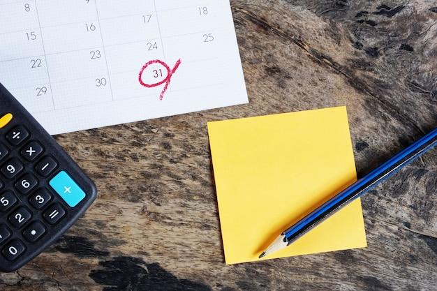 Taschenrechner, kalender, post-it-notiz und bleistift auf dem schreibtisch Premium Fotos