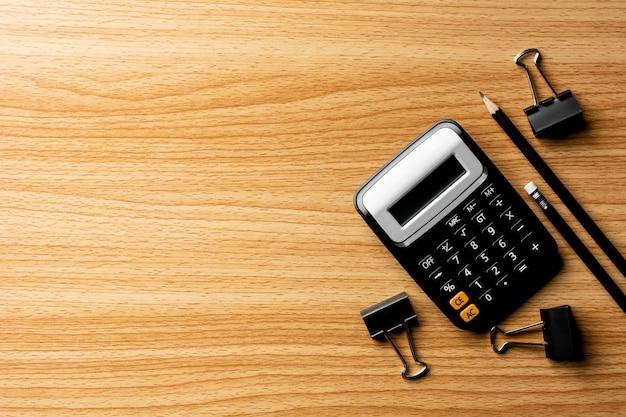 Taschenrechner und büroartikel auf holztisch. Premium Fotos