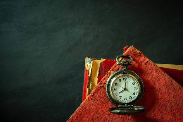 Taschenuhr und altes buch auf zementboden. Premium Fotos