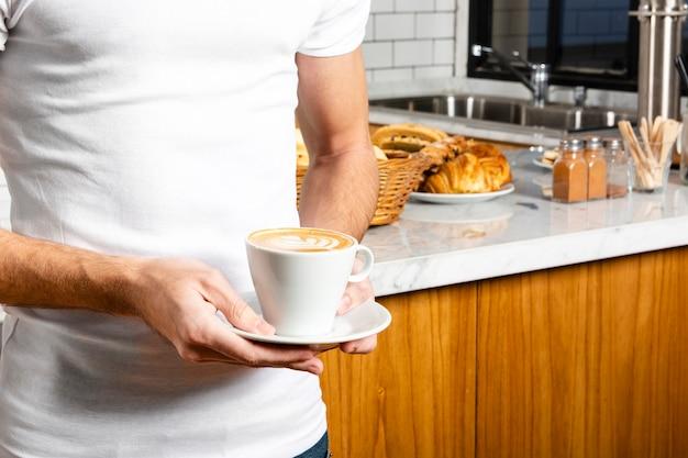 Tasse cappuccino in der hand des jungen mannes Kostenlose Fotos
