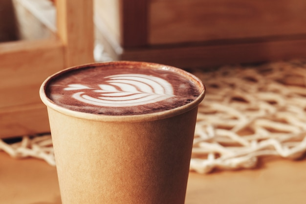 Tasse cappuccino mit einem muster auf einem tisch in einem café Premium Fotos