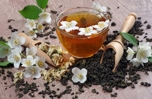 Tasse grüner tee mit jasmin auf einem holztisch. Premium Fotos