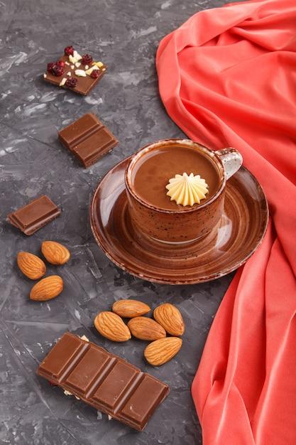 Tasse heiße schokolade und stücke milchschokolade mit mandeln Premium Fotos