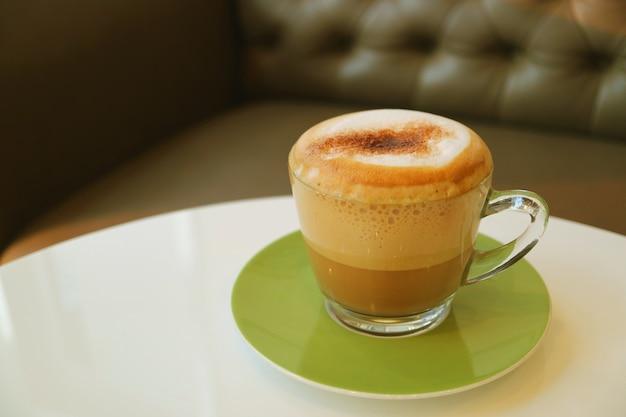 Tasse heißen cappuccino-kaffee serviert auf weißem runden tisch mit verschwommenem sofa Premium Fotos