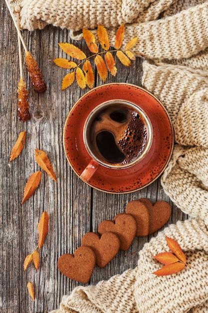 Tasse heißen schwarzen kaffee und herzförmigen lebkuchen mit herbstlichen blättern und warmen schal. Premium Fotos