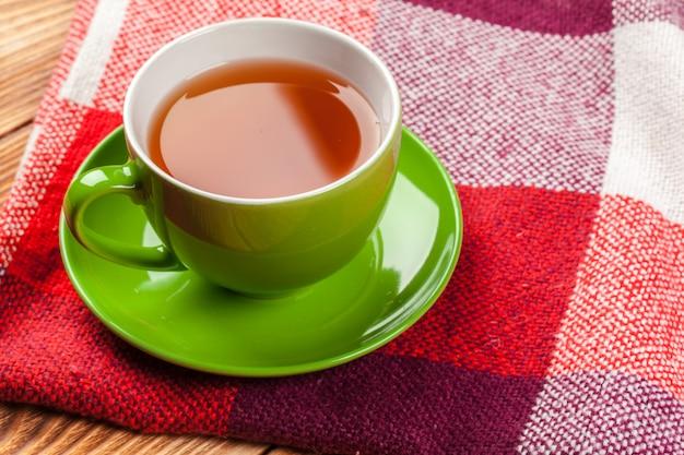 Tasse heißen tee in gestrickten warmen winterschal gekleidet Premium Fotos