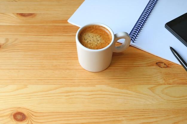 Tasse heißer kaffee mit einem notizbuch und einem mobiltelefon auf hölzernem arbeitsschreibtisch, freier raum für des Premium Fotos