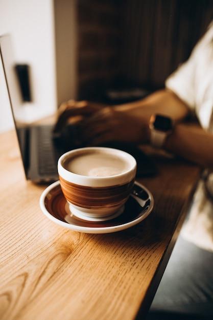 Tasse kaffee auf dem tisch neben dem laptop Kostenlose Fotos