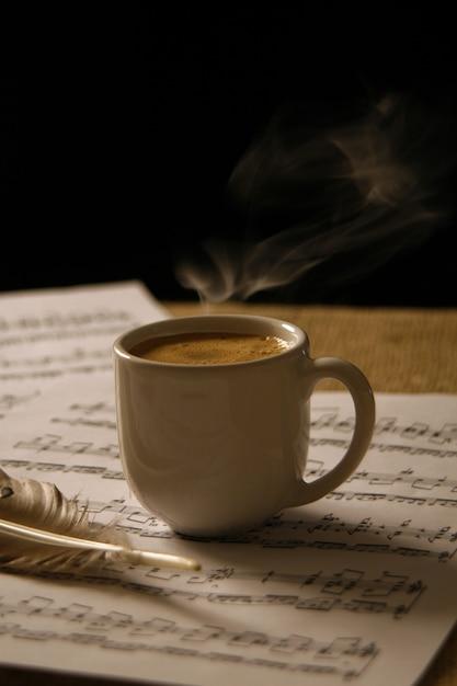 Tasse kaffee auf einer musikpartitur. Premium Fotos