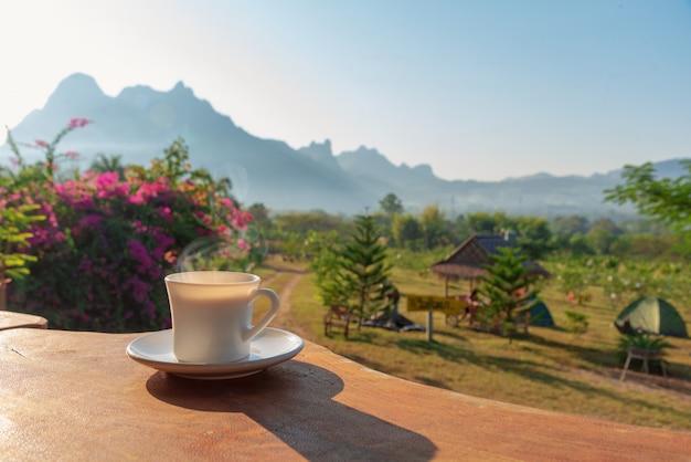 Tasse kaffee auf holztisch mit landschaft des berges und feld von anlagen im hintergrund Premium Fotos