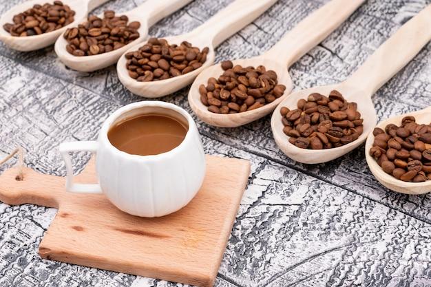 Tasse kaffee auf kleinen kaffeebohnen des hölzernen brettes im hölzernen löffel auf holzoberfläche Kostenlose Fotos
