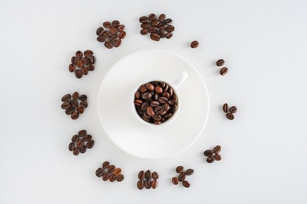 Tasse kaffee auf saucer und kaffeebohnen in form einer uhr Premium Fotos