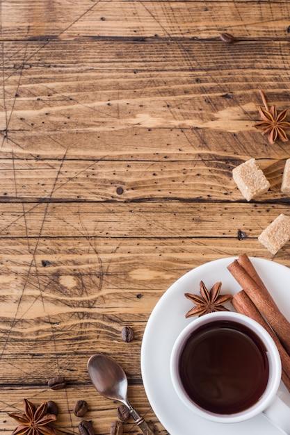 Tasse kaffee, brauner zucker und zimt mit anis auf holz Premium Fotos