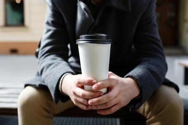 Tasse kaffee des weißen papiers, die in die arme des mannes geht Kostenlose Fotos
