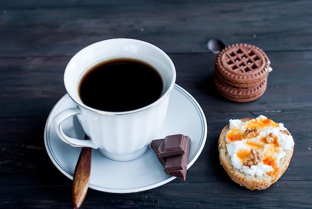 Tasse kaffee, ein sandwich mit ricotta und keksen Premium Fotos