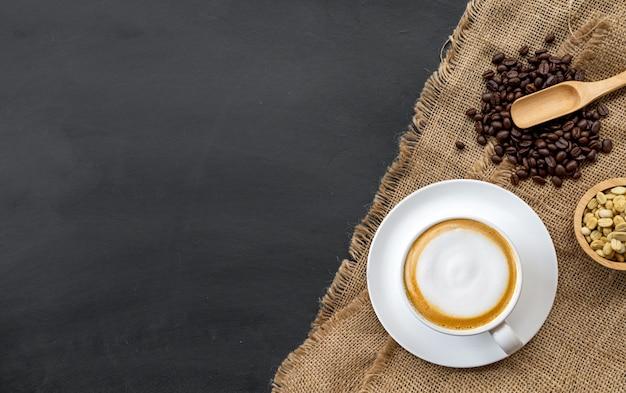 Tasse kaffee, holzlöffel und kaffeebohnen in einer schüssel Premium Fotos