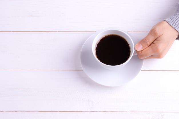 Tasse kaffee in der weiblichen hand auf weißem holztisch Premium Fotos