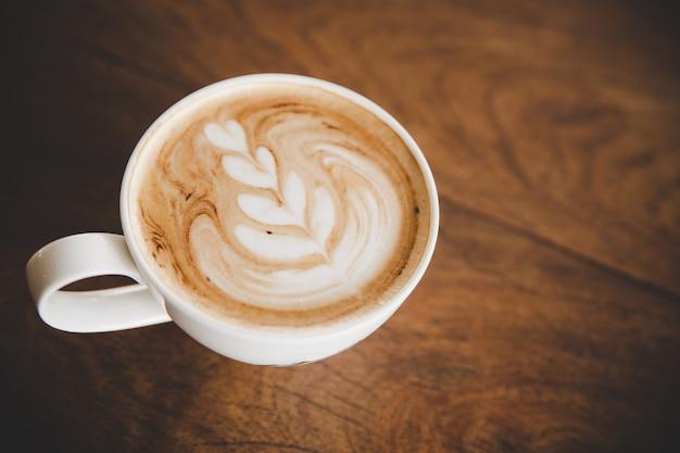 Tasse kaffee latte auf hölzerner tabelle im kaffeestubecafé Kostenlose Fotos