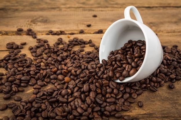 tasse kaffee liegend mit kaffeebohnen kommen aus ihm. Black Bedroom Furniture Sets. Home Design Ideas