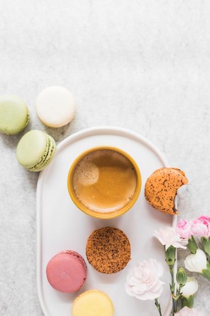Tasse kaffee mit bunten makronen mit blumen auf weißem behälter Kostenlose Fotos