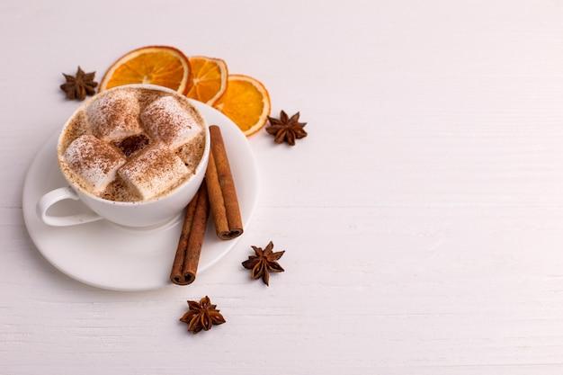 Tasse kaffee mit eibischen und kakao, blätter, getrocknete orangen, gewürze, auf einem weißen hintergrund. köstliches heißes herbstgetränk, morgenstimmung. copyspace. Premium Fotos