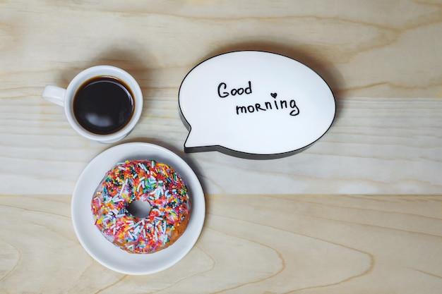 Tasse kaffee mit einem donut und einer platte auf einem holzbeschaffenheitshintergrund. konzept zum thema guten morgen. Premium Fotos