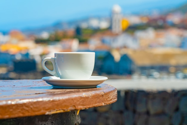 Tasse kaffee mit einer verschwommenen ansicht einer garachico-stadt am ozeanufer Kostenlose Fotos