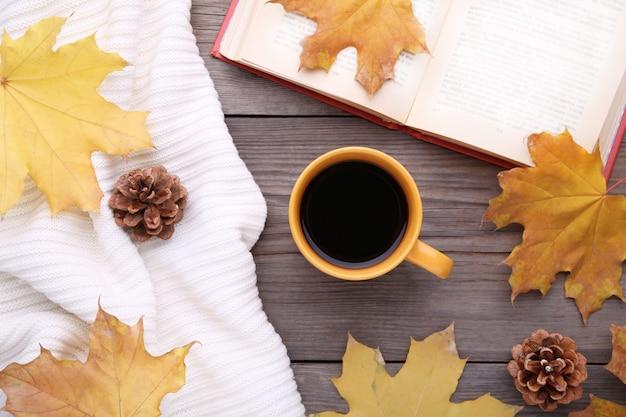 Tasse kaffee mit herbsturlaub und altem buch auf hölzernem hintergrund Premium Fotos