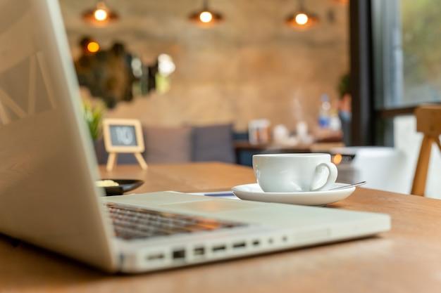 Tasse kaffee mit laptop auf tabelle in der kaffeestube. Premium Fotos