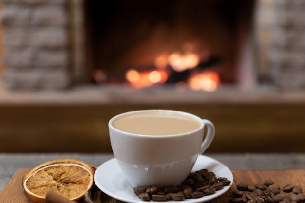 Tasse kaffee mit milch und kaffeebohnen herum, zimtstangen vor gemütlichem kamin. Premium Fotos
