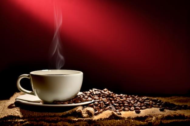 Tasse kaffee mit rauche und kaffeebohnen auf rotbraunem hintergrund Premium Fotos