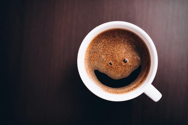 Tasse kaffee mit schaum, lächelngesicht, auf dem schreibtisch lokalisiert Kostenlose Fotos