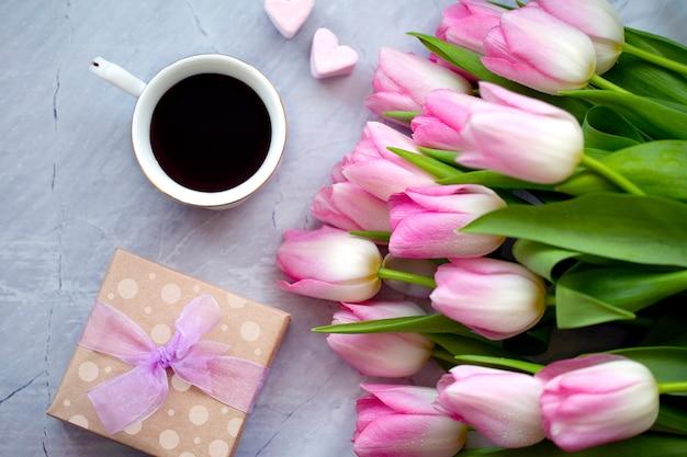 Tasse kaffee mit süßigkeiten und tulpen. geschenk für mama. konzept des frühlings. feierlicher hintergrund. blumen mit kaffee und süßigkeiten. frühstück mit blumen. Premium Fotos