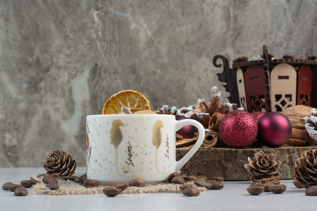 Tasse kaffee mit tannenzapfen und weihnachtskugeln auf holzteller. hochwertiges foto Kostenlose Fotos