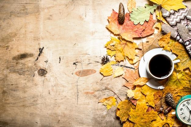 Tasse kaffee mit wecker auf herbstlaub Premium Fotos