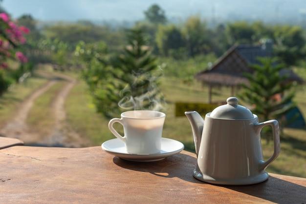 Tasse kaffee mit weißer kaffeetasse auf holztisch mit landschaft des berges und feld von anlagen im hintergrund Premium Fotos