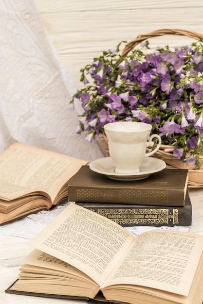 Tasse kaffee (tee), bücher und bouquet flachs im weidenkorb. retro-stil, vintage Premium Fotos