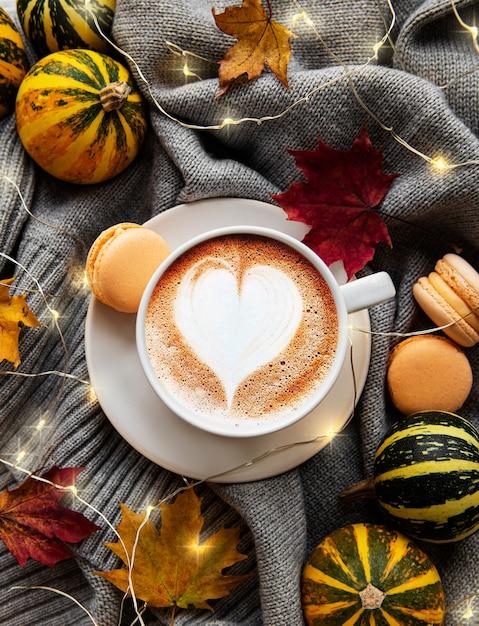 Tasse kaffee, trockene blätter und schal auf einem tisch. flache lage, draufsicht, kopierraum Premium Fotos