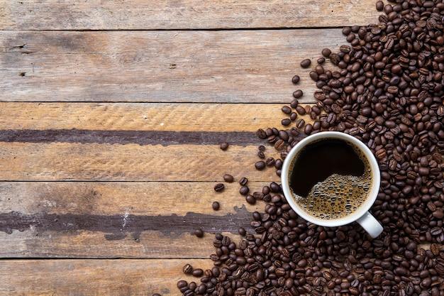 Tasse kaffee und bohne auf holzbodenhintergrund. draufsicht Premium Fotos