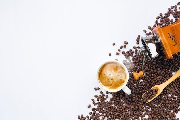 Tasse kaffee und bohne auf weißem tischhintergrund. draufsicht Premium Fotos