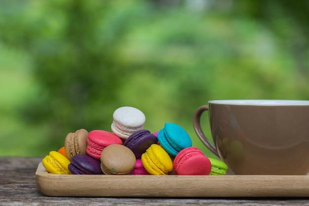 Tasse kaffee und bunte makronen im teller auf holztisch Premium Fotos