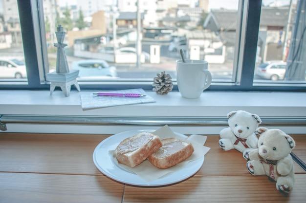 Tasse kaffee- und erdnussbutterbrot auf hölzerner bar nahe glasfenster. reisender plan zu gehen. Premium Fotos