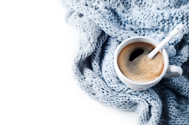 Tasse kaffee und gestrickte strickjacke auf der weißen tabelle Premium Fotos