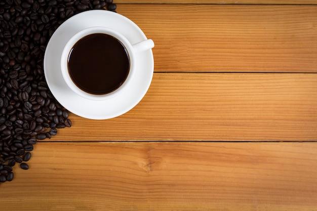 Tasse kaffee und kaffeebohnen auf holz Premium Fotos