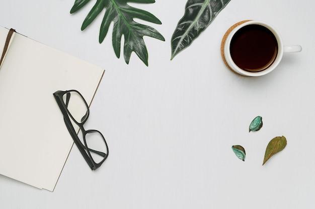 Tasse kaffee und notizbuch mit minimaler ebenenlage der gläser Premium Fotos