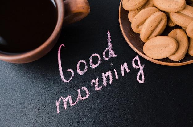 Tasse kaffee und plätzchen auf einem dunklen hintergrund. inschrift guten morgen. Premium Fotos