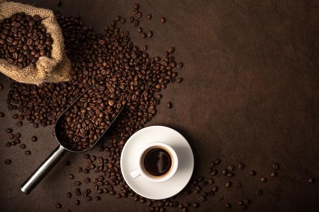 Tasse kaffee und schaufel auf braunem hintergrund. kopierbereich der draufsicht Premium Fotos
