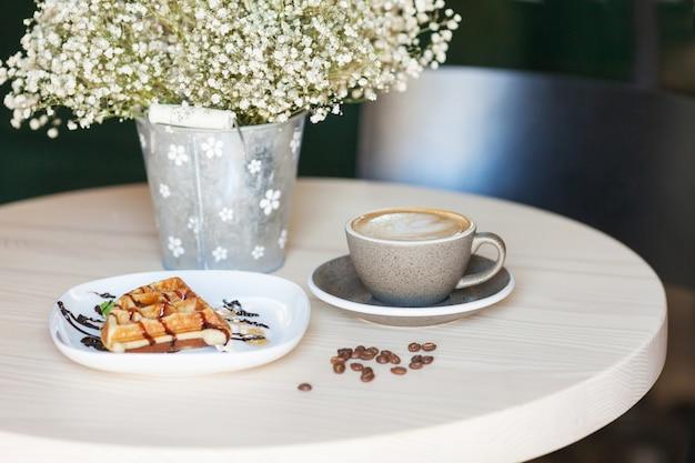 Tasse kaffee und teller mit belgischen waffeln auf hellem holztisch im café Premium Fotos