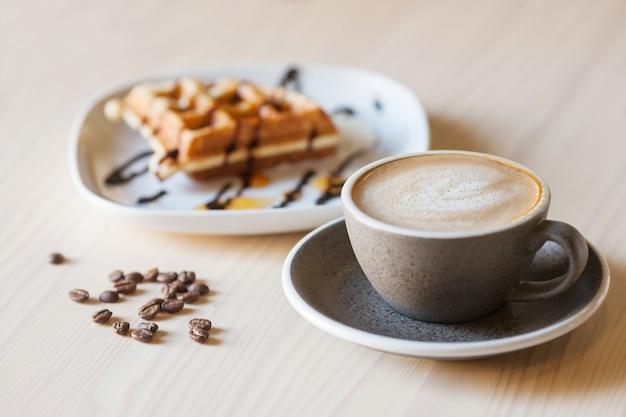 Tasse kaffee und teller mit belgischen waffeln auf hellem holztisch Premium Fotos