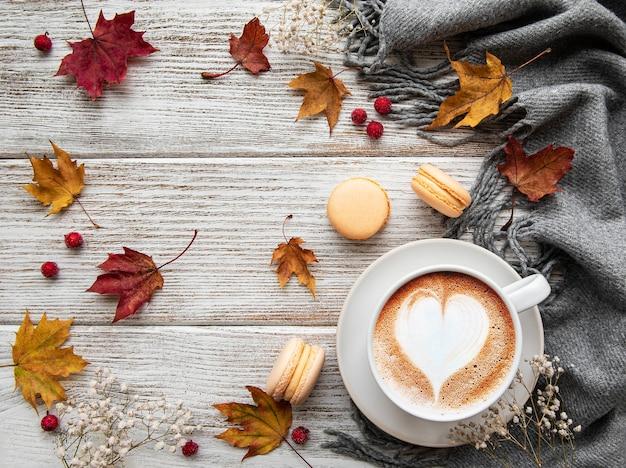 Tasse kaffee und trockene blätter auf weißem hölzernem hintergrund. flache lage, draufsicht, kopierraum Premium Fotos